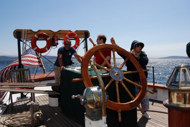 Passenger Martha, 84, takes a turn at the helm of Schooner Zodiac.