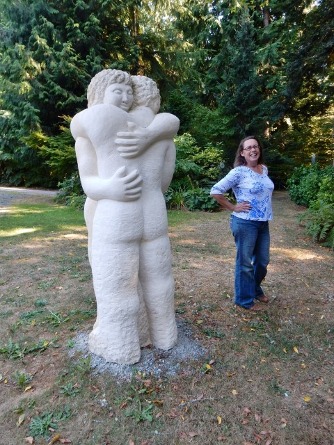 "Karla Matzke standing by sculpture ""Hug Me Like a Rock"", by Tracy Powell."